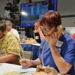 Phone volunteer Cathy Yannatta (right) takes a bid.