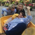 Plant sale co-chairs Halle Quinn and Chris Lippert push designer Elaine Finn in a wheelbarrow during event setup.