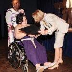 Graduate Gail Johnson receives her graduation certificate from JFS director Moira Weir