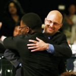 Graduate Stanley Williams hugs his mentor from the Higher Education Mentoring Initiative, Doug Cooper