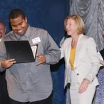 JFS Director Moira Weir presents graduate William Stiles with his graduation certificate.