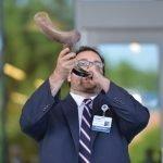 Chaplain Adam Bellows blowing the shofar, an ancient musical horn