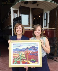 "Co-chairs Carla Landon and Tara Johnson with Wolfgang Ritschel's painting, ""Promise of the West"""