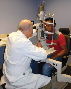 Dr. Andrew Robbins, a retired Cincinnati Eye Institute surgeon and volunteer with the CEI Foundation, with a patient