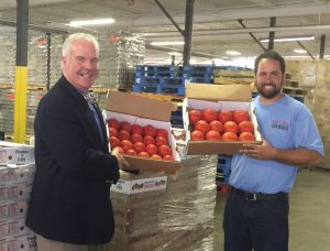 Owner Jeff Probst (right) of Blooms & Berries Farm in Loveland presents 2,000 pounds of donated tomatoes to Kurt Reiber of Freestore Foodbank.