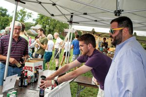 CCHURC executive director Seth Walsh and Jacob Samad serve local craft beers.