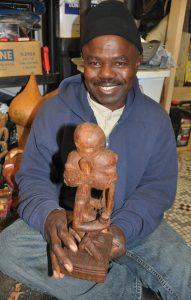 Michael Oludare holding wooden Elegbara piece
