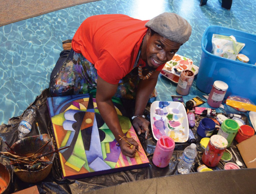 Artist Cedric Michael Cox surrounded by the tools of his trade