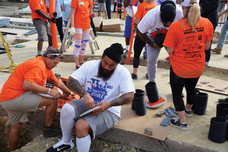 UPS volunteer Greg Schneider in orange shirt with Bengals Domata Peko and Rey Maualuga