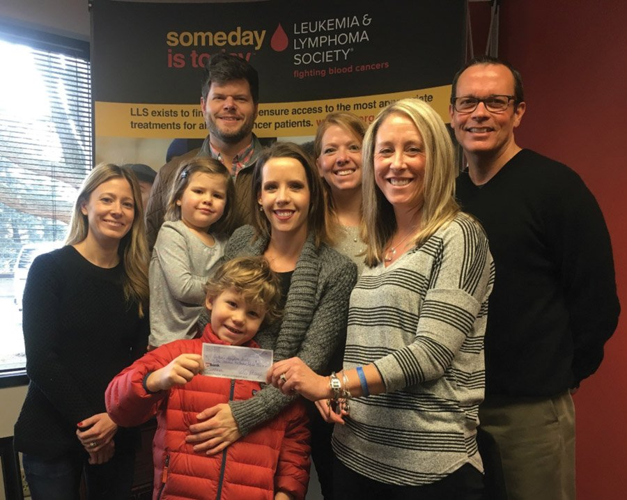 Taking part in the check presentation: (front) Lach Parry, a leukemia survivor; (middle) leukemia survivor Jen Hall, Emilie Parry holding daughter Lila; Dawn Berrman, LLS campaign director; (back) Winn Parry, Courtney Berling, who lost her mother to AML leukemia; Tom Carleton, LLS Tri-State executive director