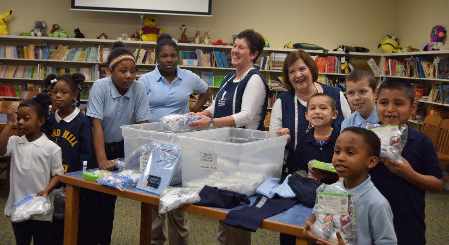 Volunteers Cyndie Willson and Betty Rothgeb provided school uniforms to students at Bond Hill Academy in Bond Hill.