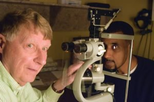 Dr. David Brounley, a retired ophthalmologist and volunteer with the CEI Foundation, with patient Brian Hills at the eye clinic at St. Vincent de Paul in Over-The-Rhine.