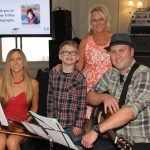Anne Rugari (in back) with her son, Phil Rugari, and his family, Stacy and PJ. Phil and Stacy performed a musical tribute to Phil's sister Gina and his brother Nick, who had Krabbe Disease.