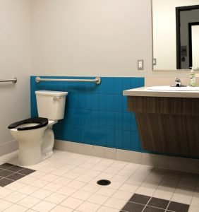 For easier navigation, the restroom has textured floors, dark tile and contrasting colors on plumbing fixtures.