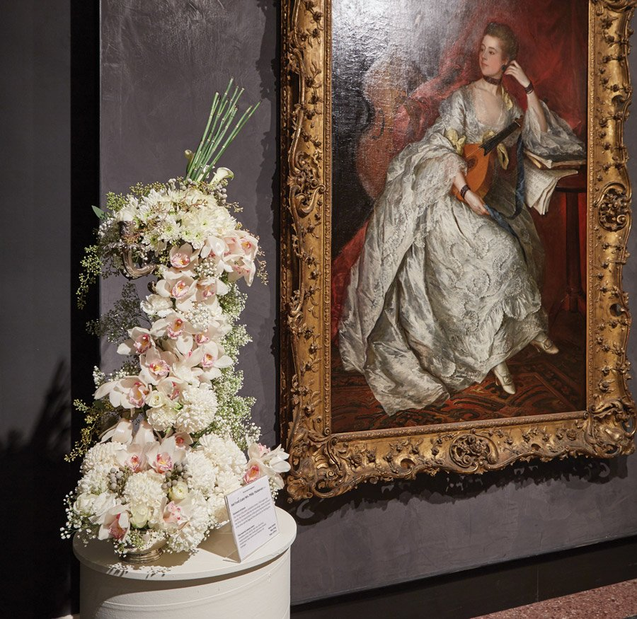 "Longtime volunteer artist Pinky Laffoon created a luscious pale rose-filled piece for the museum's beloved ""Ann Ford,"" by Thomas Gainsborough. Her floral creation was voted the favorite at the 2015 Art in Bloom."