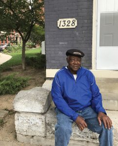 Earl Hunt, sitting on the stoop of his home in OTR