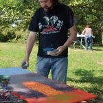 Artist Billy Tackett completing his splatter-technique piece