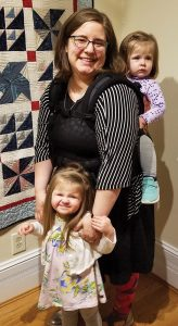 "Anna Hancock with daughters Erin and Maridith in front of her quilt, ""Airplanes and Propellers"""