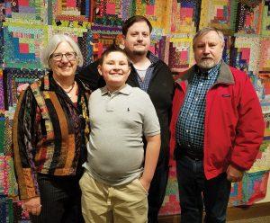 Pat Sturtzel, Landon Boone, Nick Sturtzel and Dan Sturtzel in front of a wedding quilt