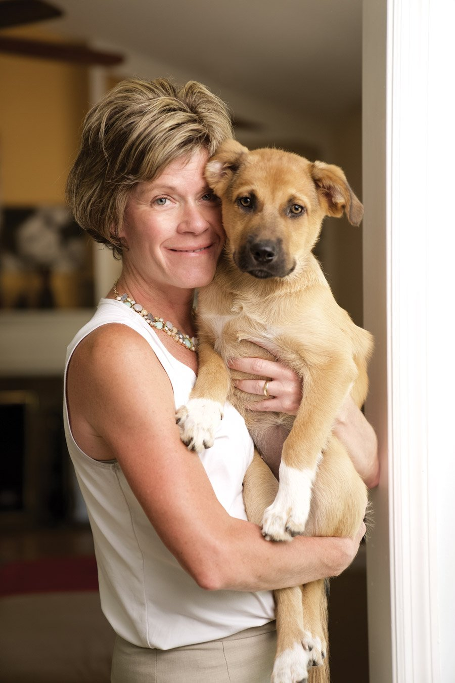 Julie Calvert, President and CEO of the Cincinnati USA Convention & Visitors Bureau, with family pet Dakotah, a rescue from Save the Animals Foundation; photo by Tina Gutierrez