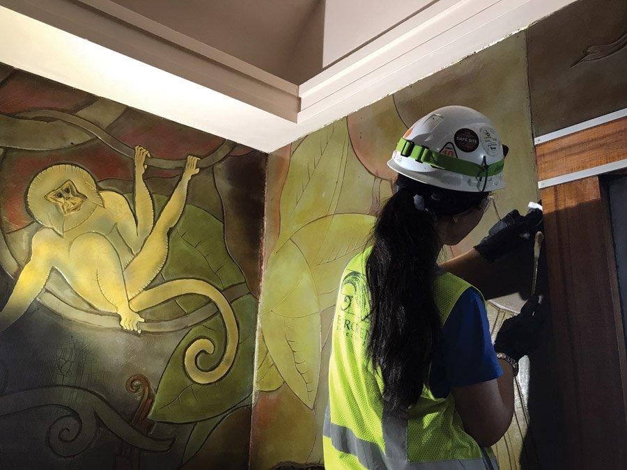 Art conservator cleaning linoleum mural.