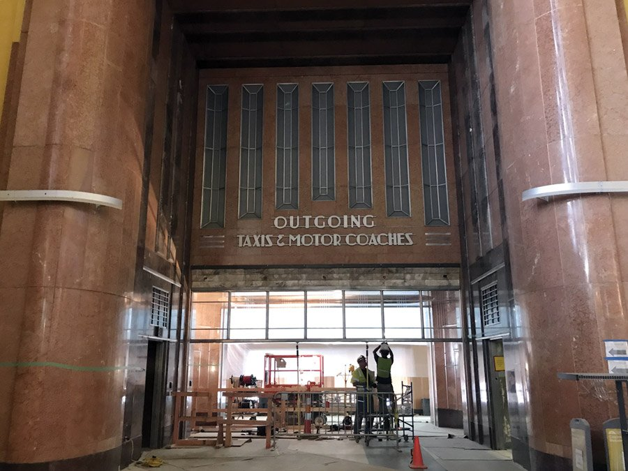 Crews work to restore aluminum frames at a museum entrance.
